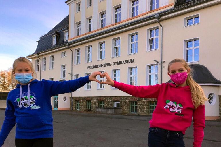 Schülerinnen vor dem Schulgebäude
